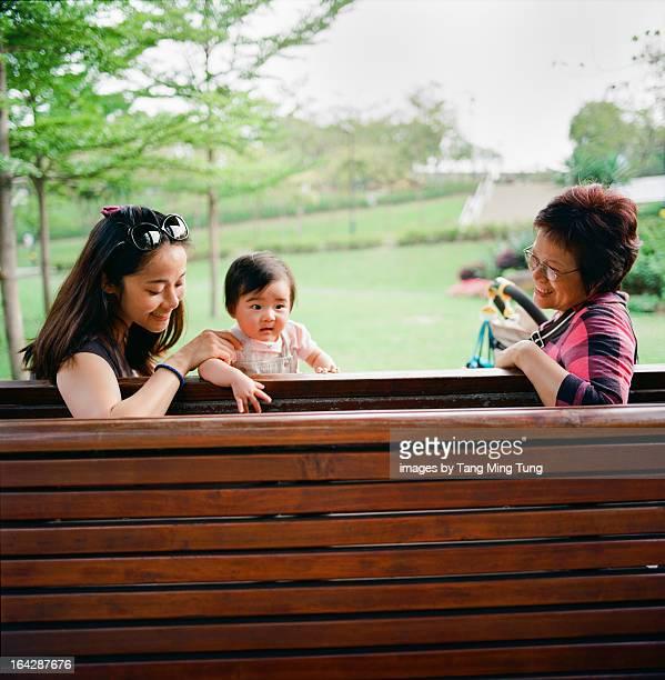 Mom ,grandma & baby enjoying family day in a park