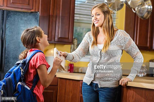 mom handing book to daughter as she leaves for school - little girls giving head stock photos and pictures