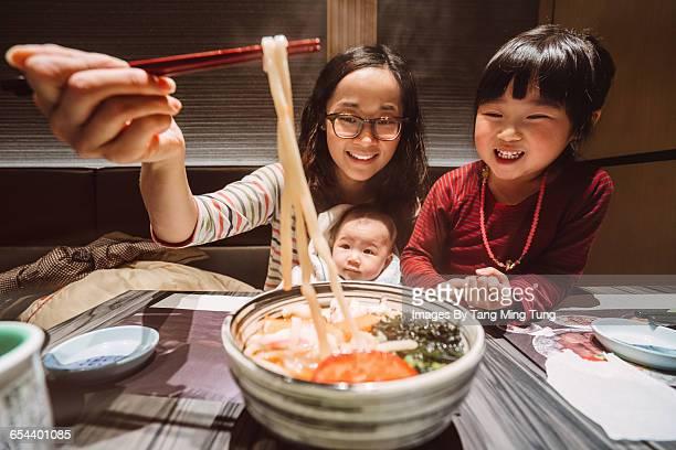 Mom having meal with lovely kids in restaurant