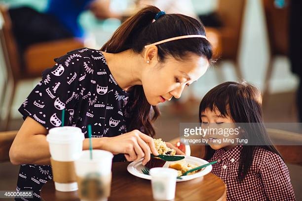 Mom having muffin with toddler girl in cafe