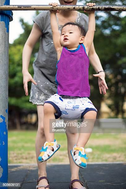 Mom help child boy to hang on horizontal bar