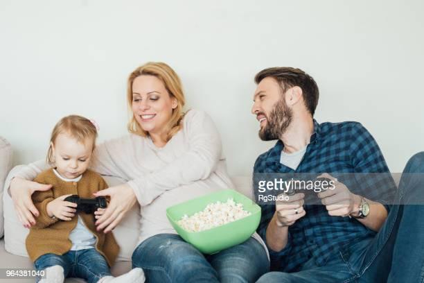 Mama hilft Baby Mädchen Halt Joystick zum Spielen von Videospielen mit Vater