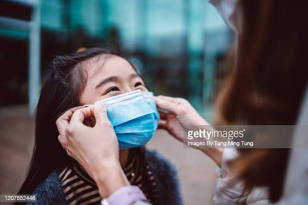 mom helping her daughter to wear medical face mask - helping hand stock pictures, royalty-free photos & images