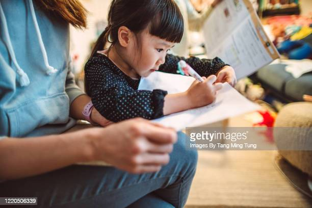 mom helping her little daughter with homework at home. - hong kong stock pictures, royalty-free photos & images