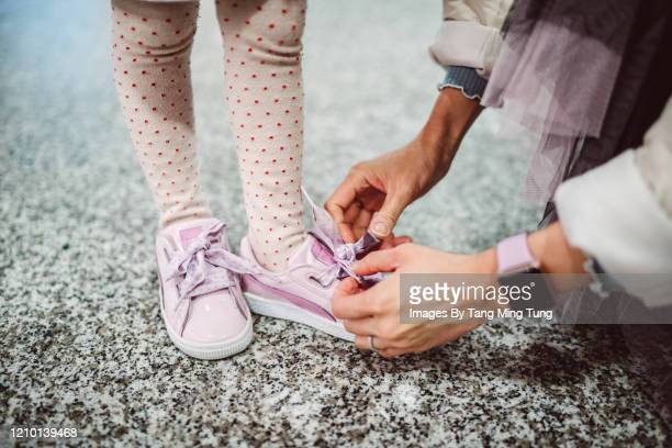mom helping little girl to tide her shoelace - childhood stock pictures, royalty-free photos & images