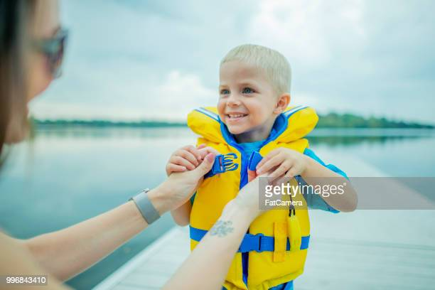 mom helping out - life jacket stock pictures, royalty-free photos & images