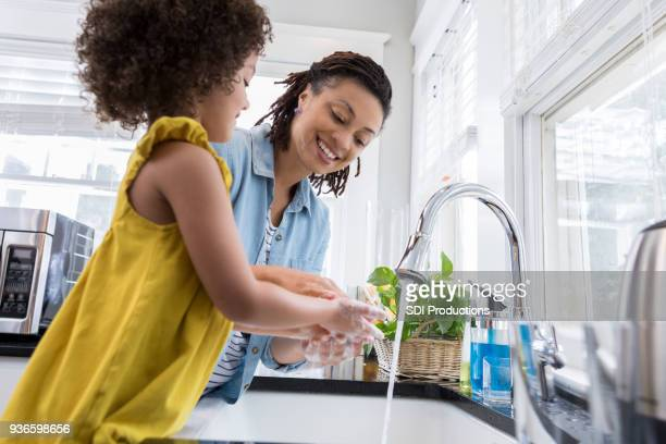 mom helping young daughter wash hands - lavandino foto e immagini stock