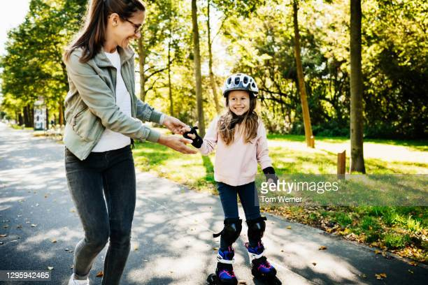 mom helping young daughter while learning to roller blade - skate sports footwear stock pictures, royalty-free photos & images