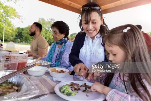 ママは娘が食事中に食べ物をカットするのに役立ちます - ポットラック ストックフォトと画像