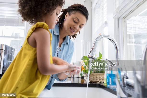mom helps daughter wash hands - running water stock pictures, royalty-free photos & images