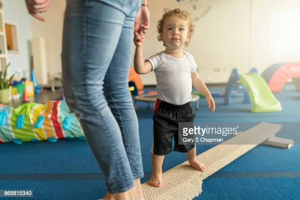 A mom helps her son on balance beam at gym class for toddlers
