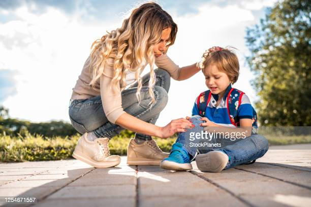 mom helps her son with injured knee - knee length stock pictures, royalty-free photos & images