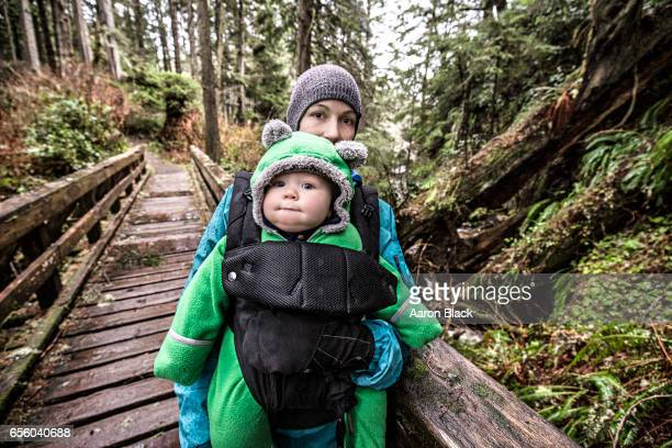 Mom hikes with baby on bridge in lush forest.