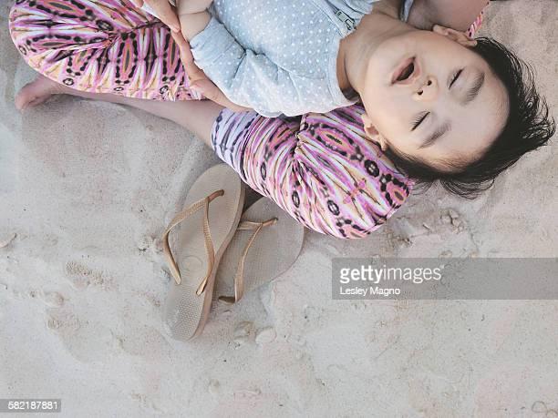 Mom holding a baby sleeping at Bondi Beach