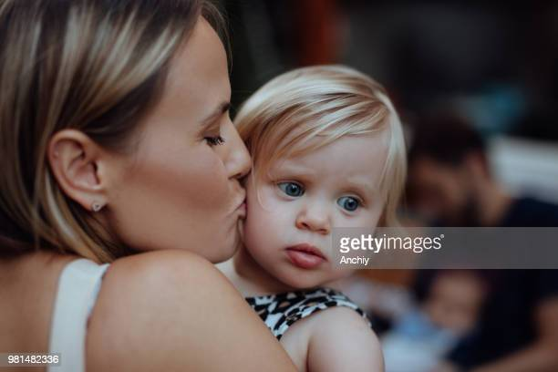 Mom holding and kissing cute little girl over her shoulder