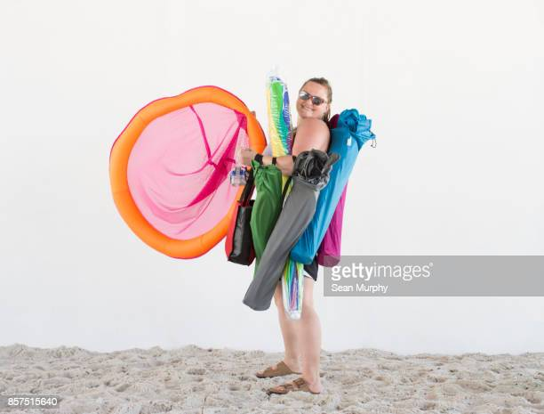 mom holding beach toys on sand with white backdrop - destin beach stock pictures, royalty-free photos & images