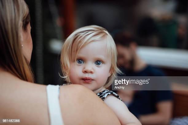 Mom holding cute little girl over her shoulder