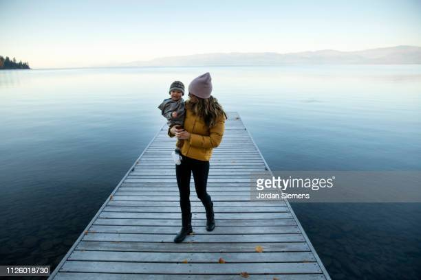 a mom holding her young son on a dock. - blue jacket stock pictures, royalty-free photos & images