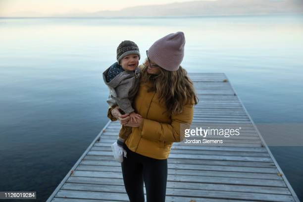 A mom holding her young son on a dock.