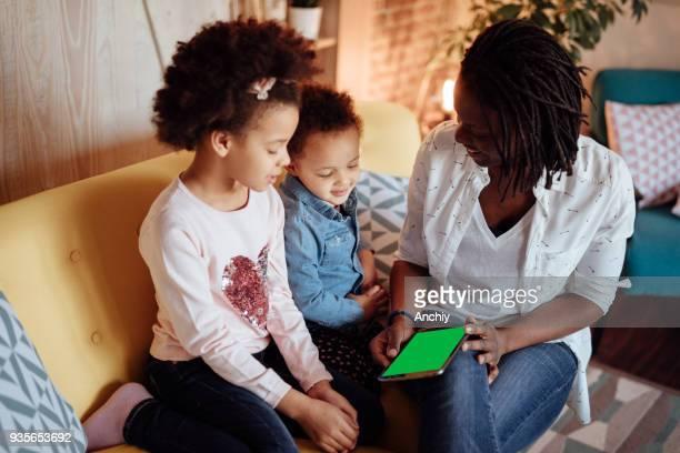 Maman tenant la tablette pour les filles à regarder