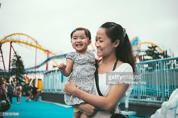 Mom holding toddler in amusement park joyfully