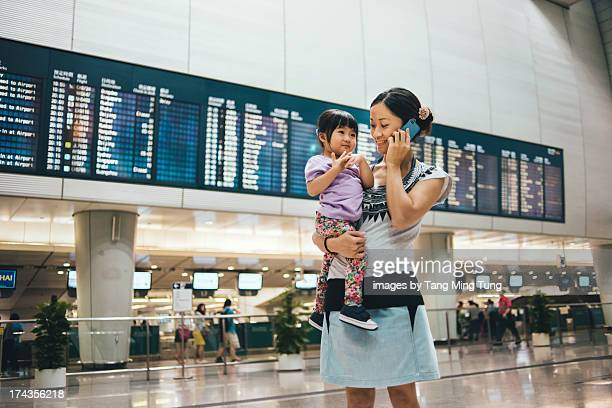 mom holding toddler talking on mobile in airport - toddler at airport stock pictures, royalty-free photos & images