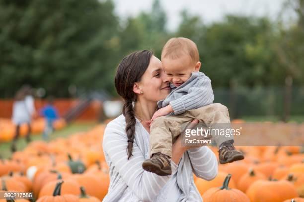 Maman brandissant son jeune fils mignon au champ de citrouilles