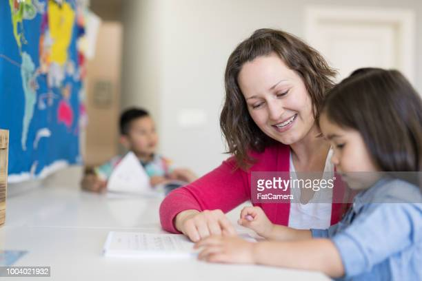 mom homeschooling her young children - montessori education stock pictures, royalty-free photos & images