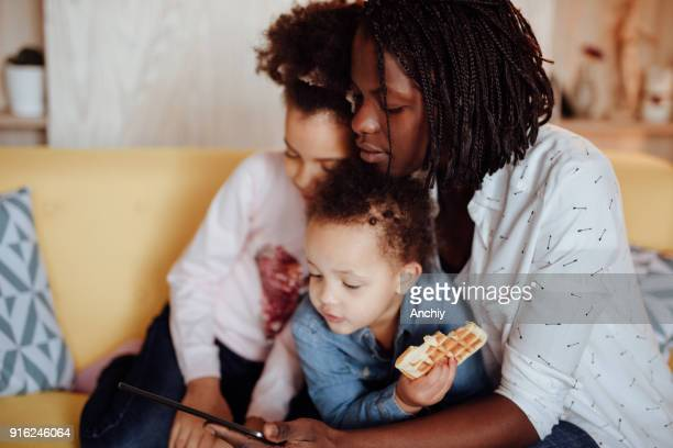mom hugging her daughters and watching cartoons on tablet - interracial cartoon stock photos and pictures