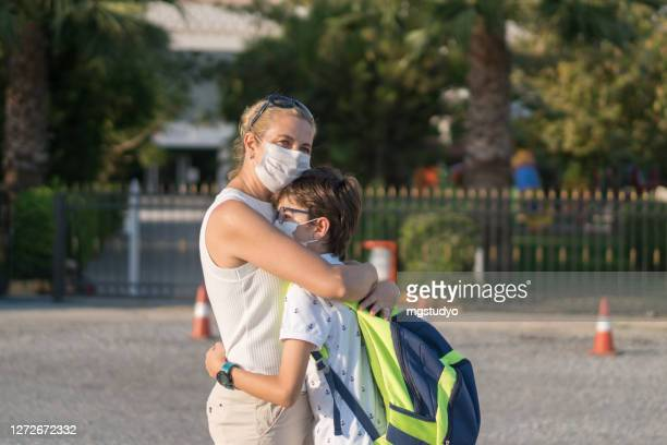 mom hugging her son in front of the schoolyard - turkey middle east stock pictures, royalty-free photos & images
