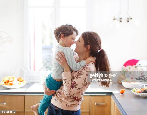 A mom hugging her son in the kitchen