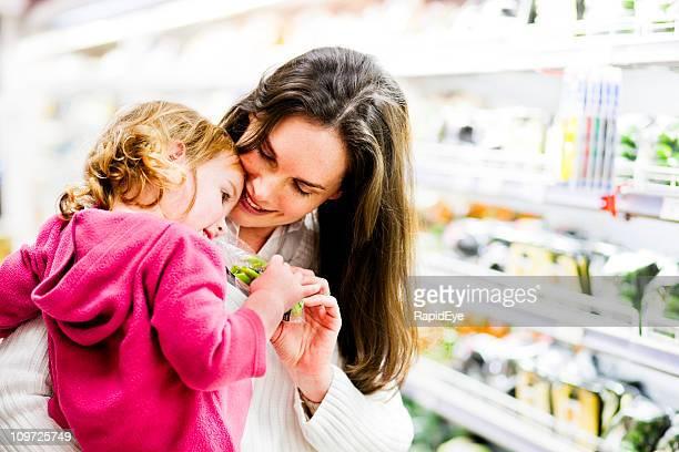 Maman câlins fille dans un supermarché