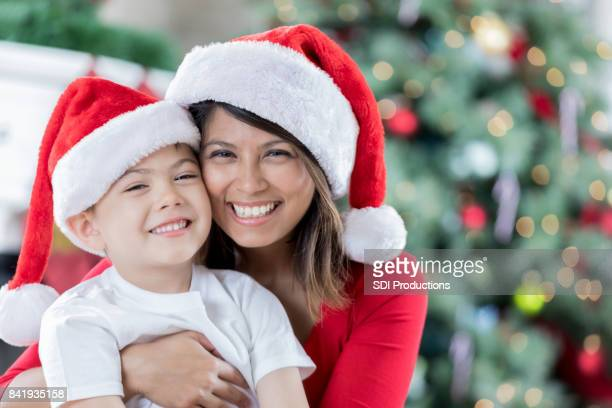 mom hugs son on christmas morning - filipino christmas family stock pictures, royalty-free photos & images