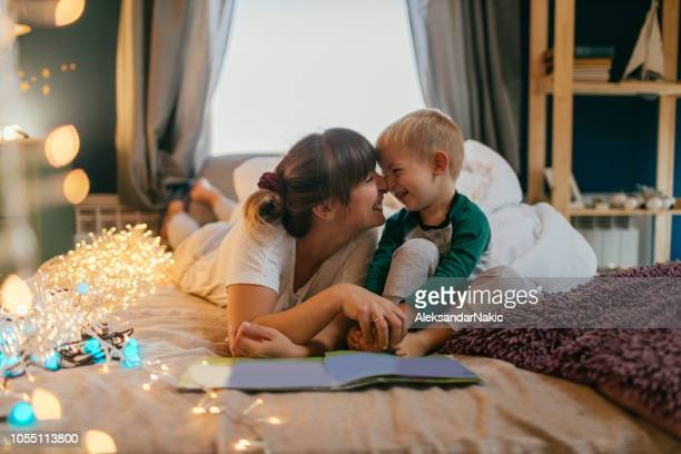 mom is reading bedtime stories - family with one child stock pictures, royalty-free photos & images