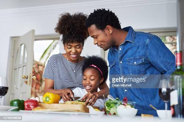 mamá les está enseñando cómo cocinar - black cook fotografías e imágenes de stock