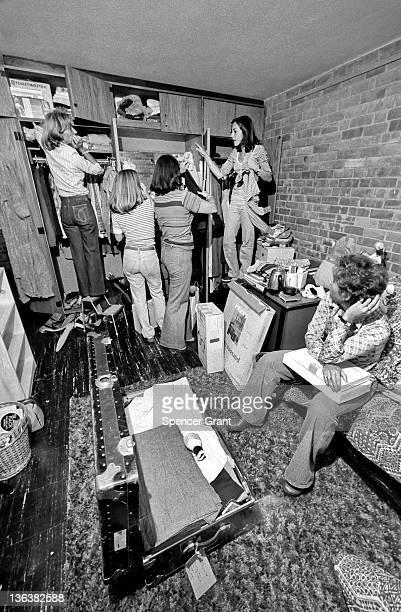 Mom joins in as Jackson freshman girls unpack in their new dorm room Medford Massachusetts mid 1970s