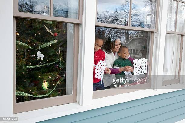Mom & kids taping homemade snowflakes on window