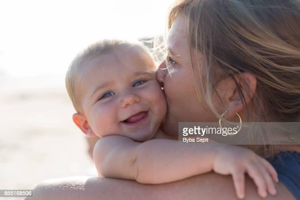 mom kisses toddler on a cheek. - affectueux photos et images de collection