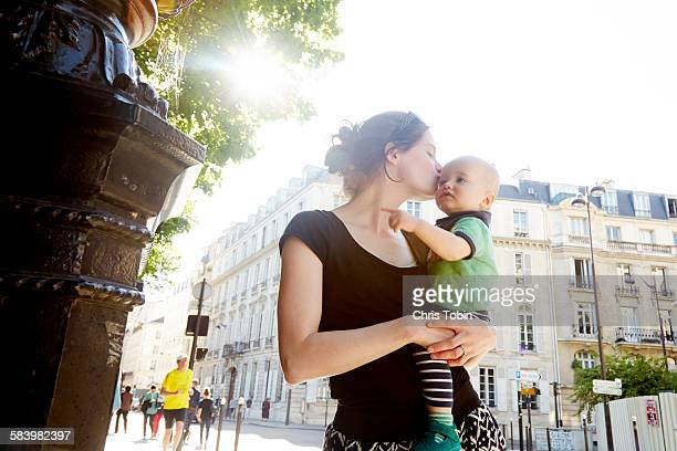 Mom kissing baby in Paris