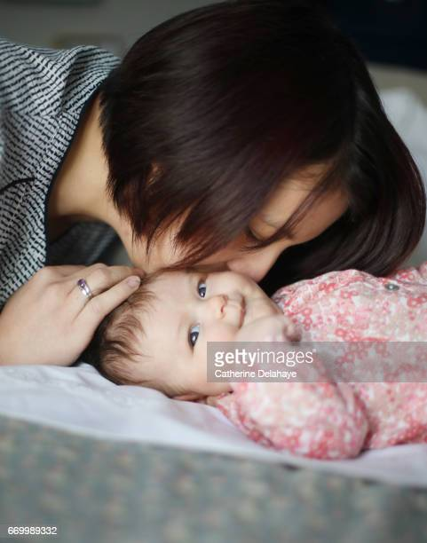 A mom kissing her 2 months old baby girl