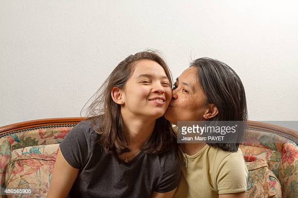 mom kissing her daughter - jean marc payet stock pictures, royalty-free photos & images