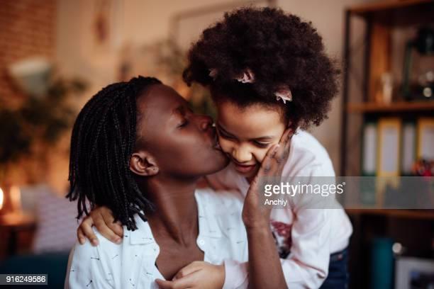 お母さんの娘にキス - interracial cartoon ストックフォトと画像