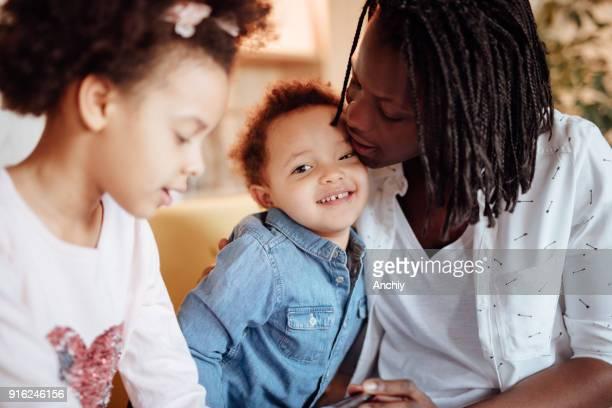 お母さんの額で若い娘のキス - interracial cartoon ストックフォトと画像