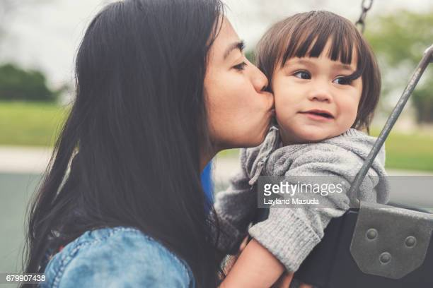 mom kissing toddler at the playground - asian baby stock photos and pictures