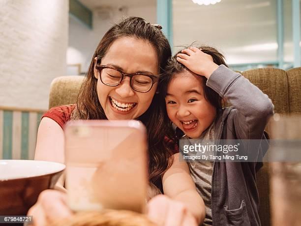 Mom & little daughter taking selfie in restaurant