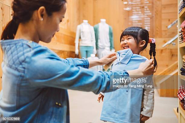Mom & little girl shopping kid's wear in shop