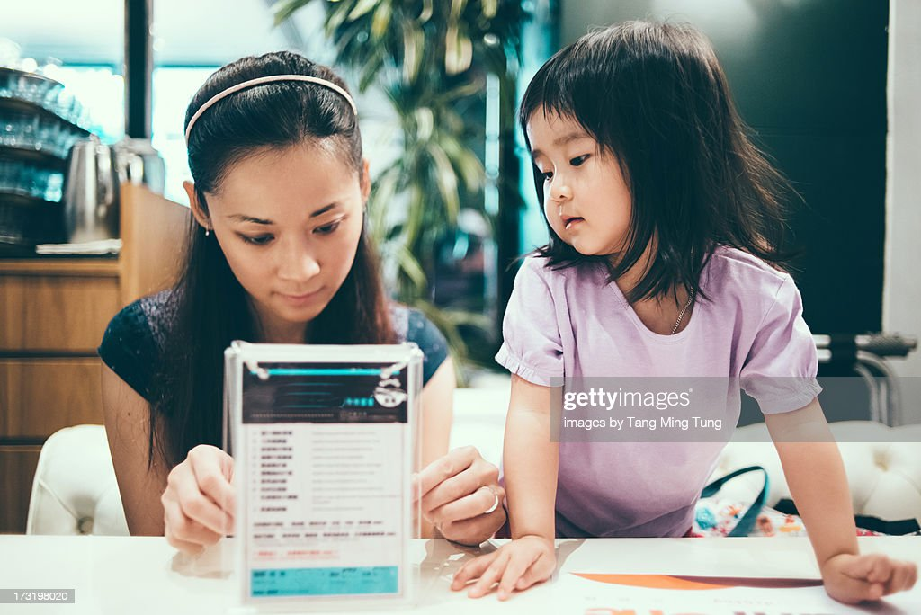 Mom looking at menu with toddler in restaurant : Stock Photo