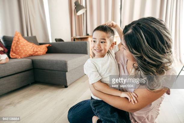 mom lovingly staring at her son - mom sits on sons lap stock pictures, royalty-free photos & images