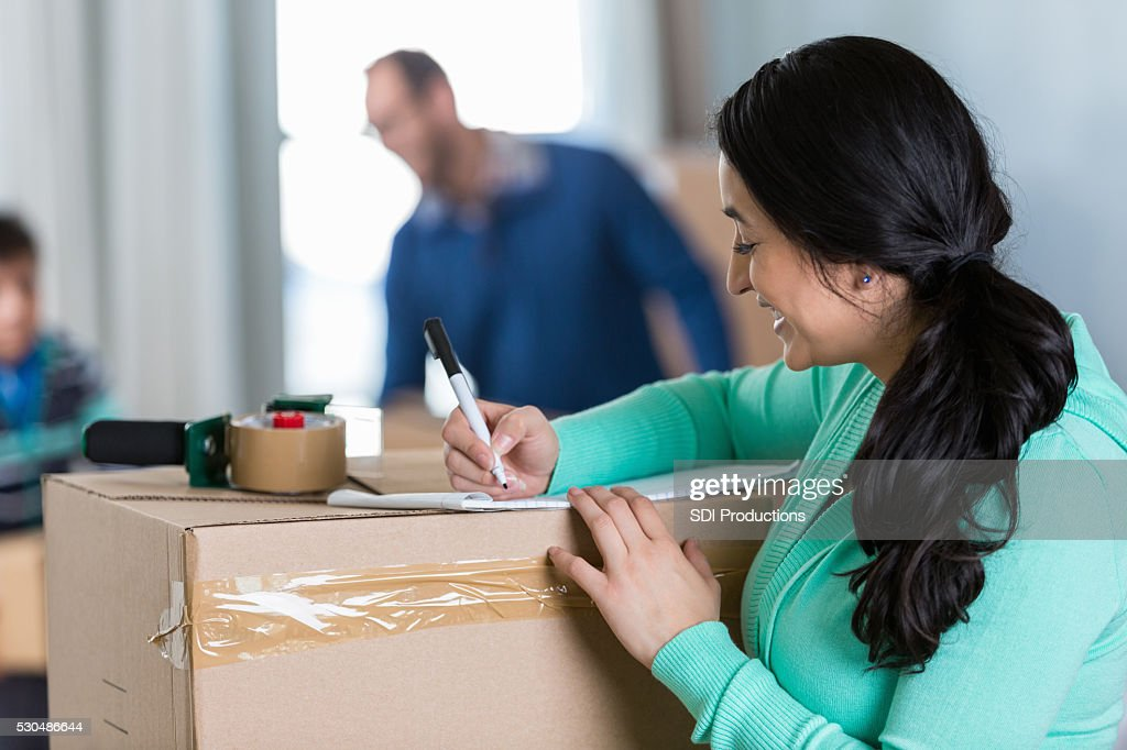 Mom makes list while preparing to move to new home : Stock Photo