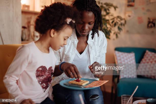 mom making breakfast for her daughter - interracial cartoon stock photos and pictures